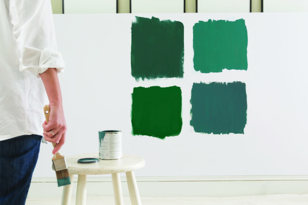 Woman trying green paint color swatches on wall