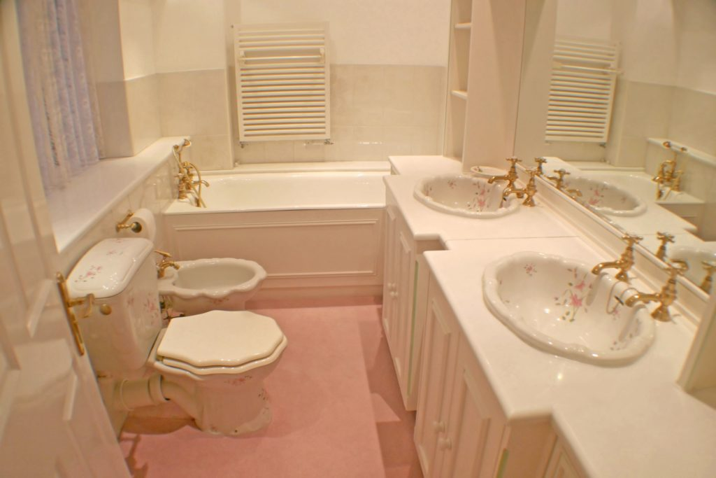 Dated bathroom with pink wall-to-wall carpeting